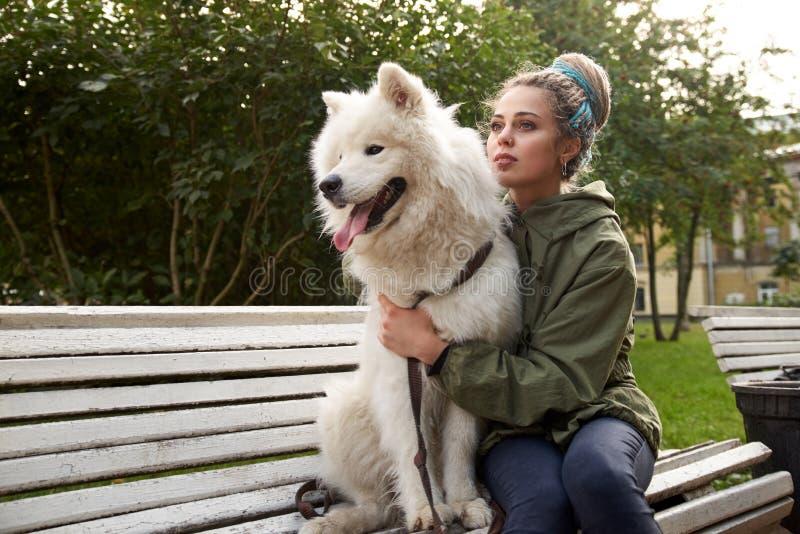 En attraktiv ung kvinna med dreadlocks sitter på en parkerabänk med hennes snövita Samoyedhund arkivfoto