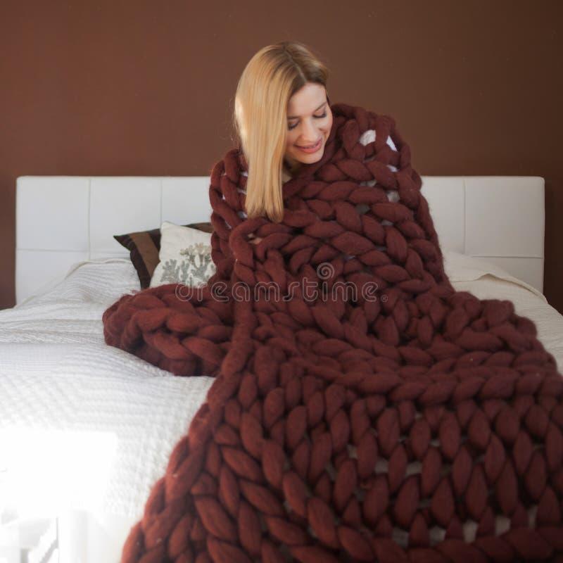 En attraktiv ung kvinna sl?s in i en mjuk fluffig filt royaltyfria foton
