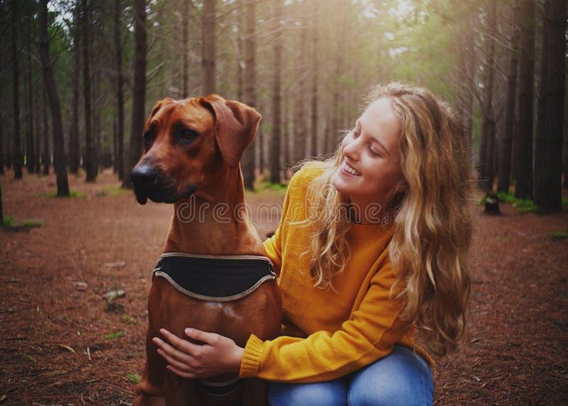 En attraktiv ung kvinna som älskar hennes lydiga hund royaltyfri foto