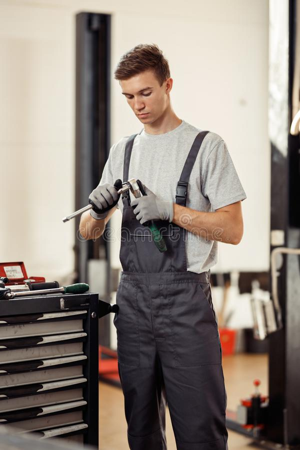 En attraktiv ung man som rymmer speciala instrument i hans händer, är på arbete i en bilservice arkivfoto