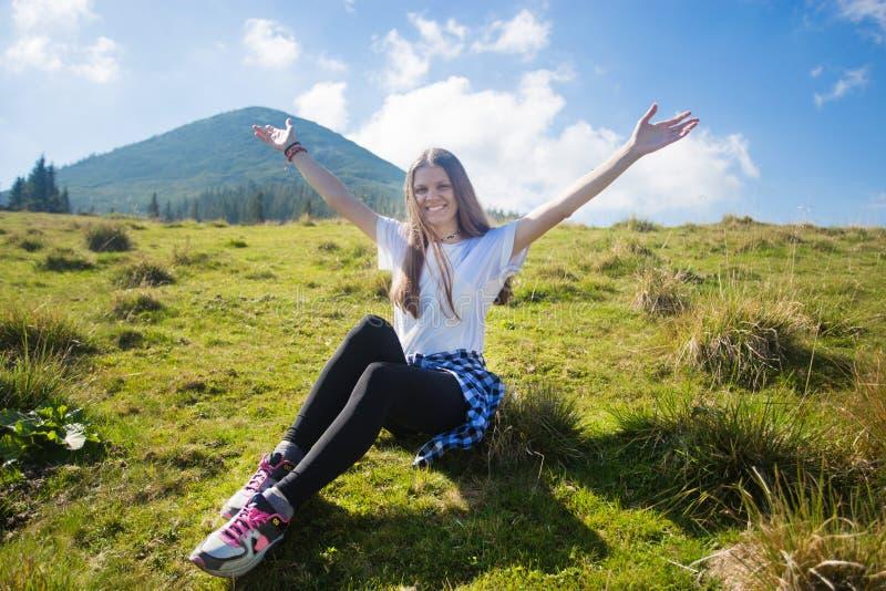 En augmentant la fille sur la colline avec des mains appréciez le Mountain View photographie stock