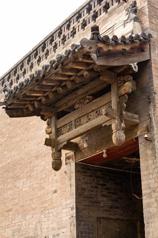 En av de typiska träsned garneringarna ovanför tillträdesdörrarna av Pingyao den forntida staden, Shanxi landskap, Kina royaltyfria foton
