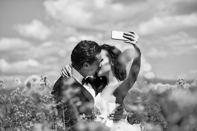 En avundsvärd brudgum gifta sig parkyssen i fältgulingblommor royaltyfria foton