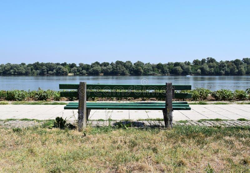 En bänk vid floden fotografering för bildbyråer