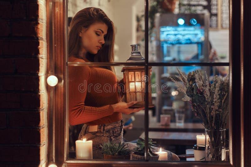 En bärande tröja för härlig flicka som rymmer en stearinljuslykta, medan sitta på en fönsterfönsterbräda inom kafét arkivbild