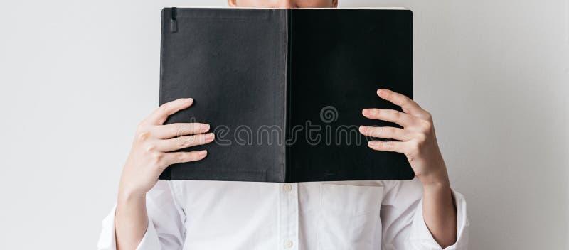En bärande vit skjorta för man och rymma en svart räkningsbok framme av honom arkivfoton
