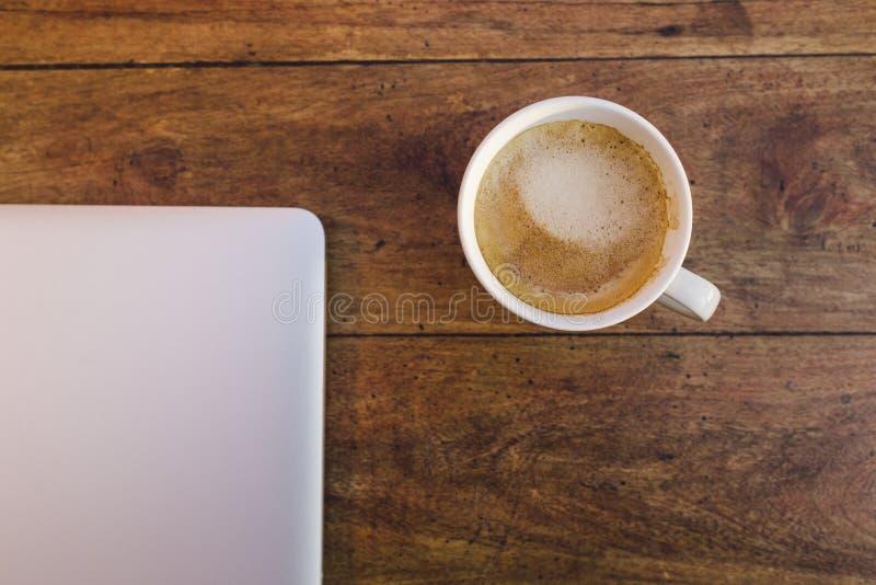 En bärbar dator och en kopp kaffe över en wood tabell royaltyfri foto