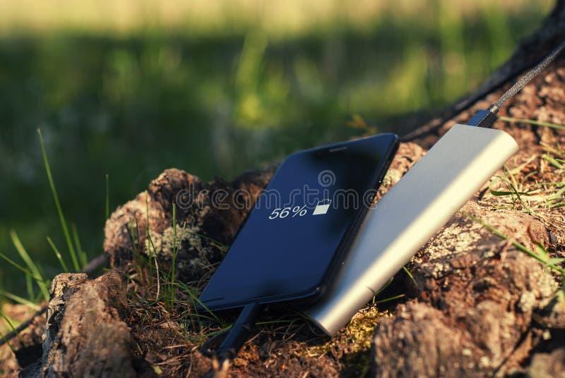 En bärbar uppladdare laddar smartphonen Driva banken med kabel mot bakgrunden av trä fotografering för bildbyråer