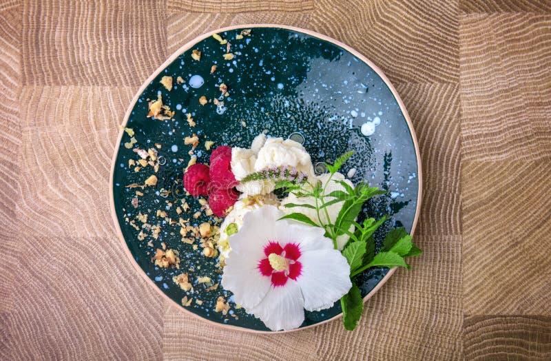 En bästa sikt av en platta mycket av en glass med söta rosa hallon på en träbakgrund Organiska och nya mellanmål royaltyfria foton