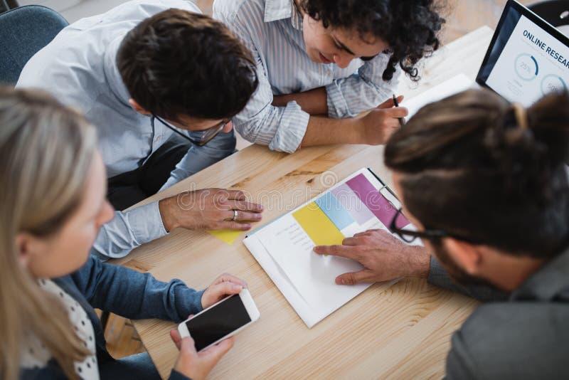 En bästa sikt av gruppen av unga businesspeople som tillsammans arbetar i ett modernt kontor arkivbild
