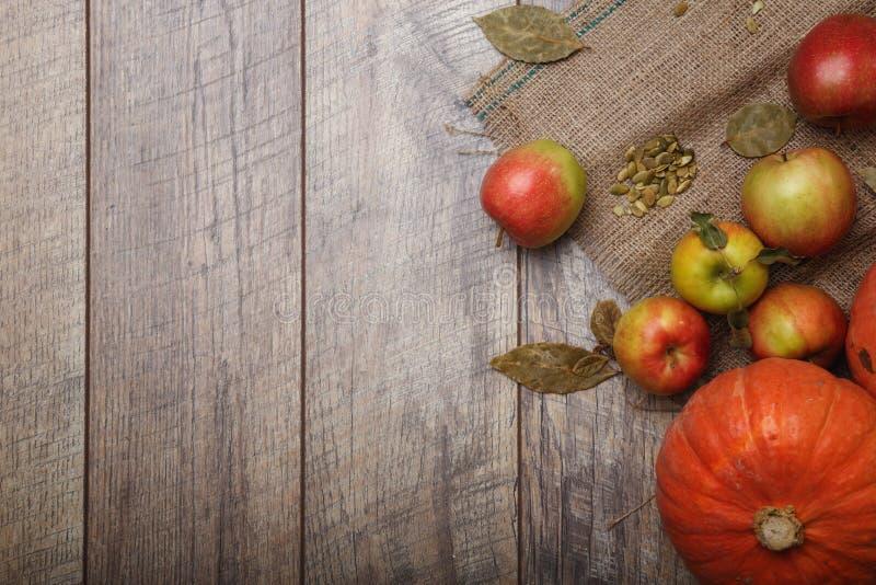 En bästa sikt av ljusa två ljusa pumpor och färgrika äpplen på en lantlig torkduk på en träbakgrund kopiera avstånd royaltyfria bilder