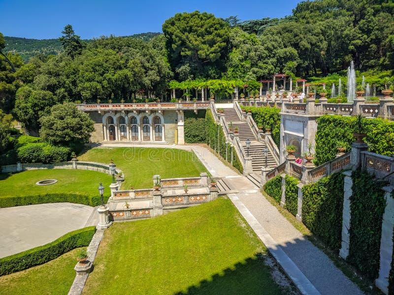 En bästa sikt på trädgården av Miramare kast på sjösidan av Adriatiskt havet En härlig trädgård med höga träd och grönt gräs är royaltyfria bilder