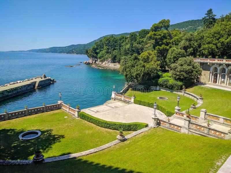 En bästa sikt på trädgården av Miramare kast på sjösidan av Adriatiskt havet En härlig trädgård med höga träd och grönt gräs är arkivfoton