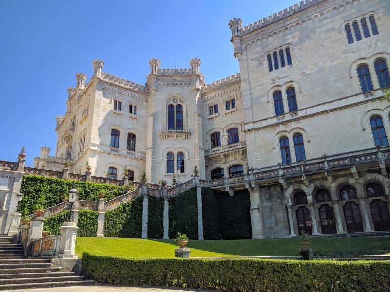 En bästa sikt på trädgården av Miramare kast på sjösidan av Adriatiskt havet En härlig trädgård med höga träd och grönt gräs är royaltyfri bild