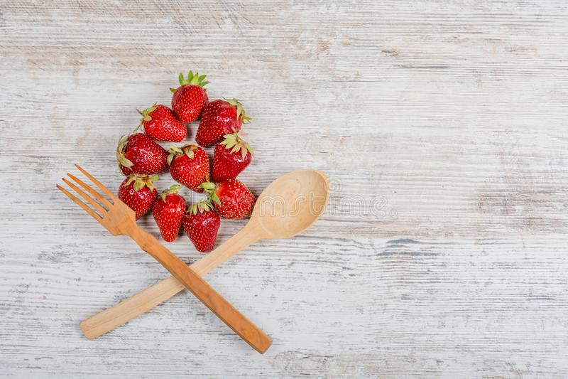 En båge av ny mogen röd strawberriesSummervitaminmat Massor av nya mogna doftande jordgubbar och en träsked och gaffel royaltyfria bilder