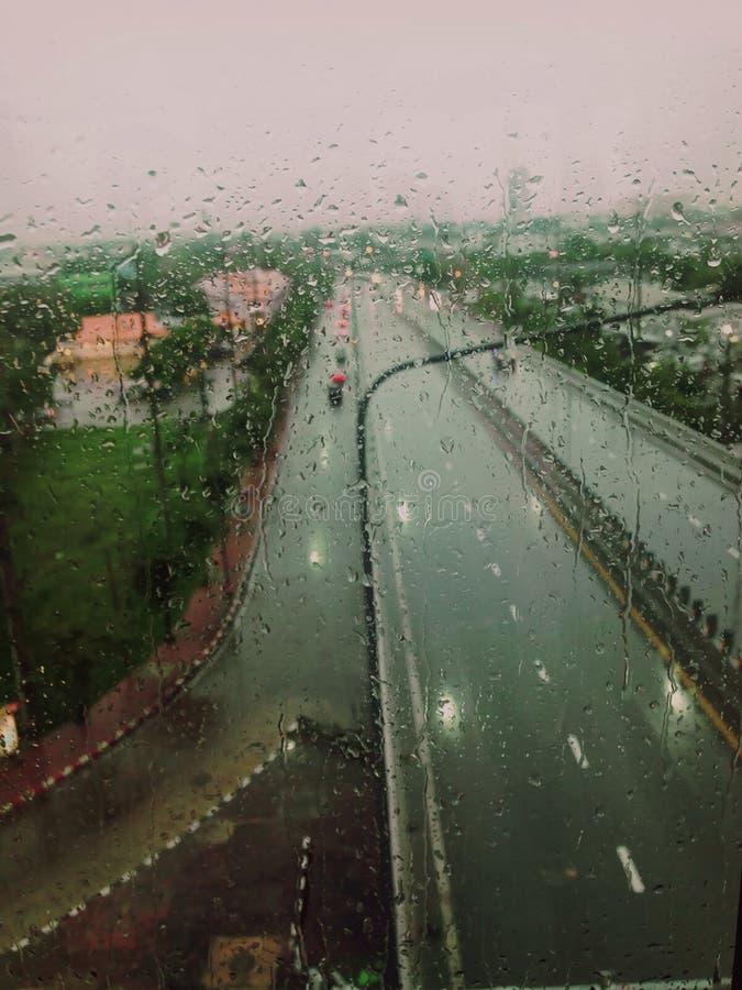 En bakgrund på gatan och regndroppen på fönster arkivfoton