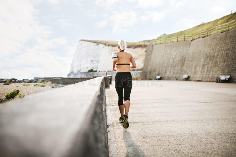 En bakre sikt av den unga sportiga kvinnalöparen som kör utanför på en strand i natur royaltyfri fotografi