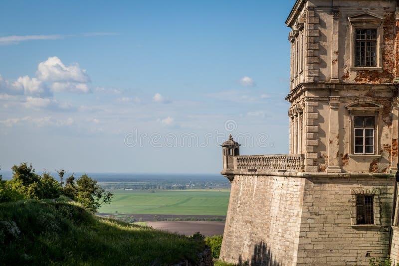 En balkong av den medeltida Pidhirtsi slotten med ett fält på bakgrund royaltyfria foton