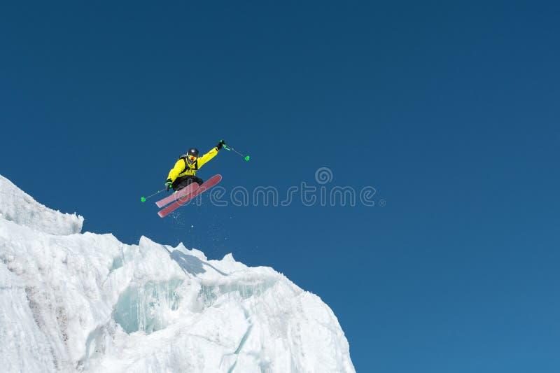 En banhoppningskidåkarebanhoppning från en glaciär mot en blått som är skyhög i bergen Yrkesmässig skidåkning royaltyfri fotografi