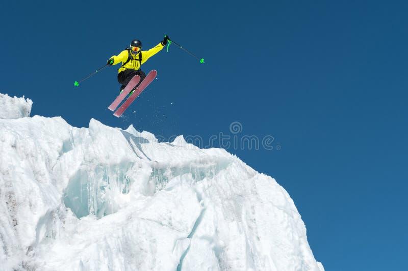 En banhoppningskidåkarebanhoppning från en glaciär mot en blått som är skyhög i bergen Yrkesmässig skidåkning arkivbilder