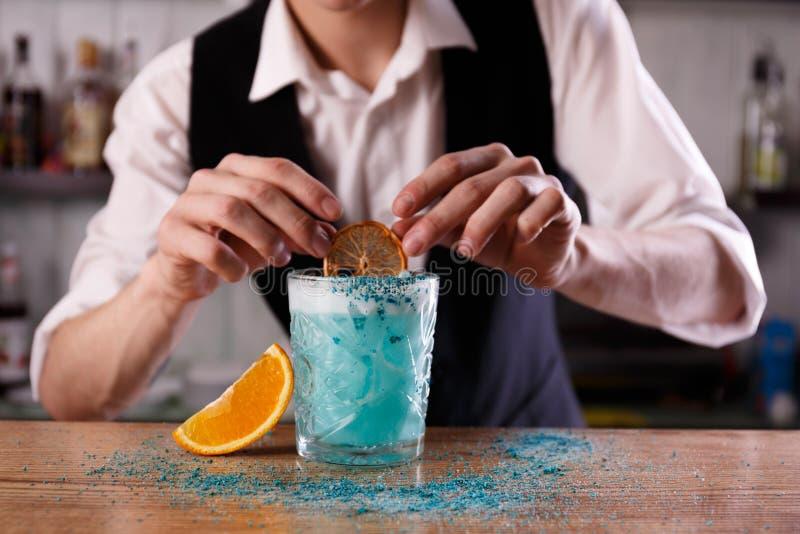 En bartender förbereder en blå laguncoctail fotografering för bildbyråer
