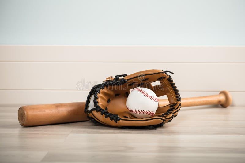 En baseballutrustning på golv royaltyfria bilder