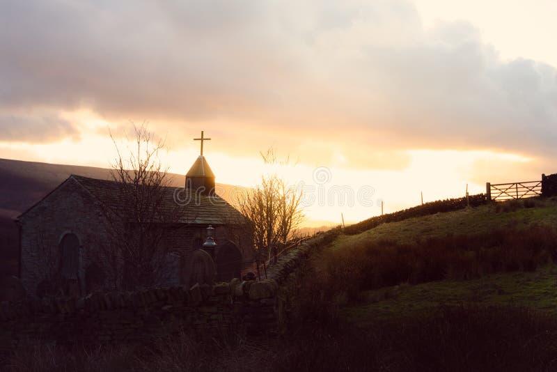 En bedöva bild av en kyrka som tas på solnedgången med solen bakom royaltyfria bilder