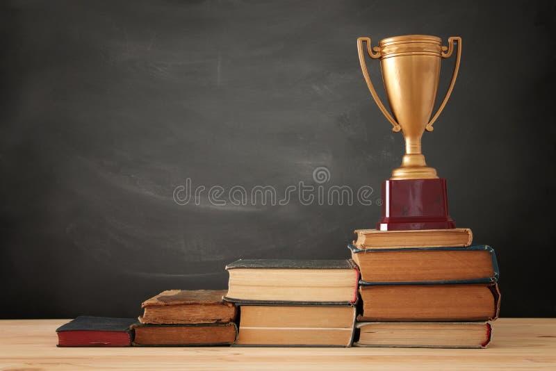 En begreppsbild av utbildningsframgång, en bunt av böcker som överst ordnas som en pyramid med den guld- trofén royaltyfria foton