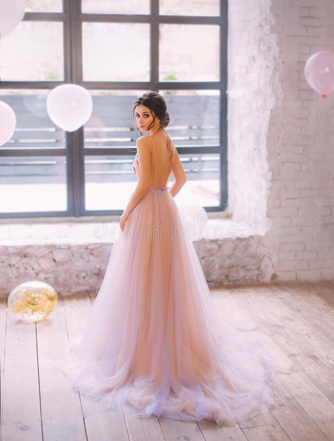 En behagfull ung dam med mörkt hår i en ursnygg mjuk lång persika och en purpurfärgad klänning med ett drev och en öppen baksida, arkivbilder