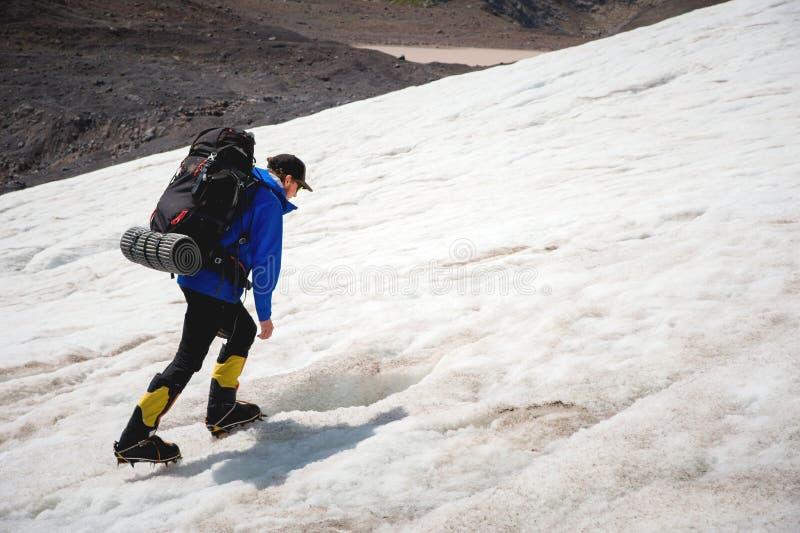 En bergsbestigare med en ryggsäck går i isbroddar som promenerar en dammig glaciär med trottoarer i händerna mellan sprickor royaltyfri fotografi