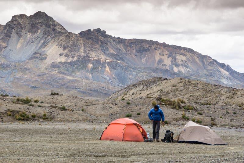 En bergsbestigare och två tält i en avlägsen basläger i den Cordillera Blancaen arkivfoton
