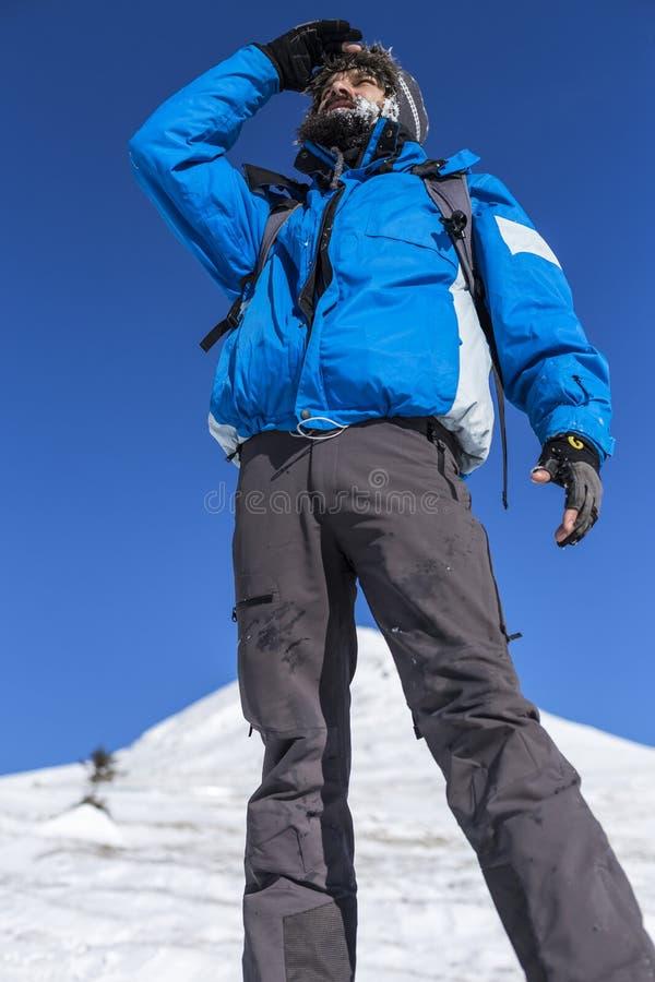 En bergsbestigare på överkanten av ett snöig berg arkivbilder