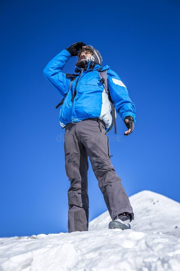 En bergsbestigare på överkanten av ett snöig berg royaltyfri bild