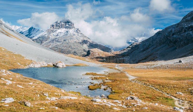 En bergsjö i höst med berg som täckas med insnöad bakgrund arkivfoto