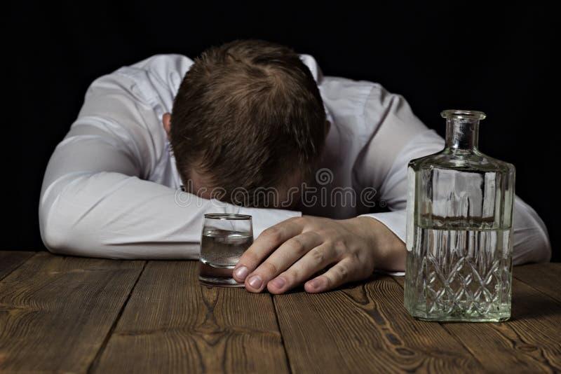 En berusad affärsman ligger på en tabell, i hans hand ett skott av vin med alkohol, en svart bakgrund, alkoholist arkivbilder