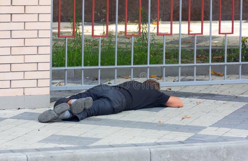 En berusad hemlös man som ligger på trottoaren arkivbilder