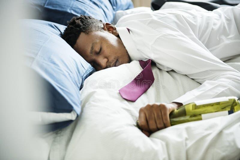 En berusad man som är övergående ut i säng arkivfoto