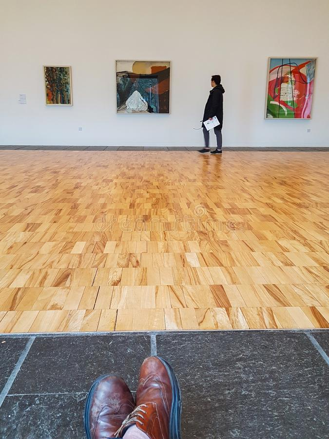 En besökare ser målningar inom Whitworthen Art Galle arkivfoton