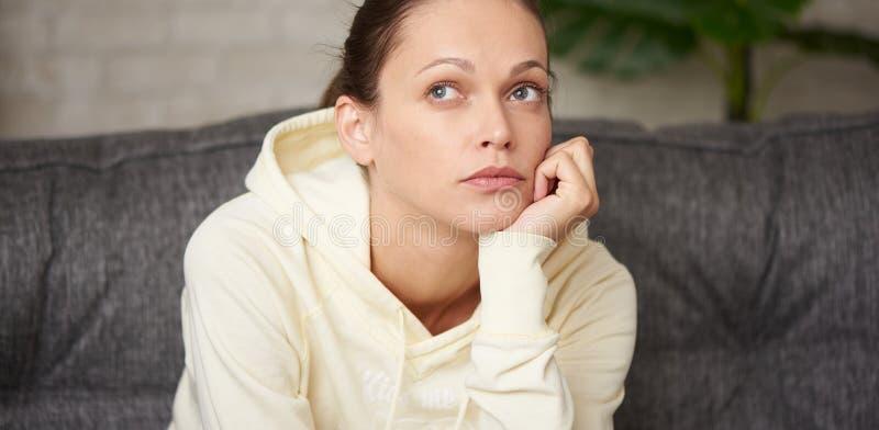 En bestraffande vacker kvinna tittar upp och tänker på något arkivbild