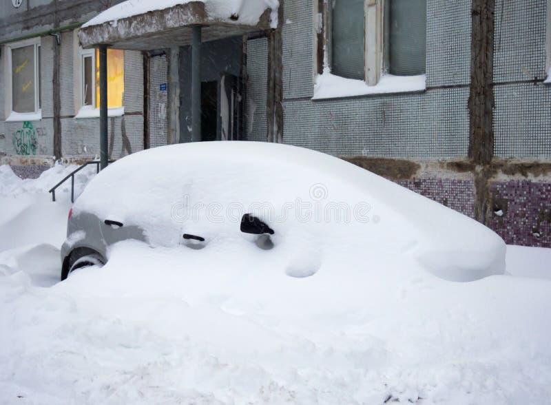 En bil i en snödriva nära ingången av en bostads- byggnad royaltyfria foton