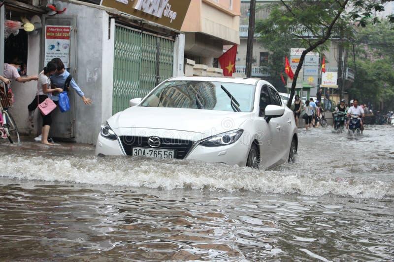En bil kör i floden i mitten av den Hanoi staden i Vietnam royaltyfria foton
