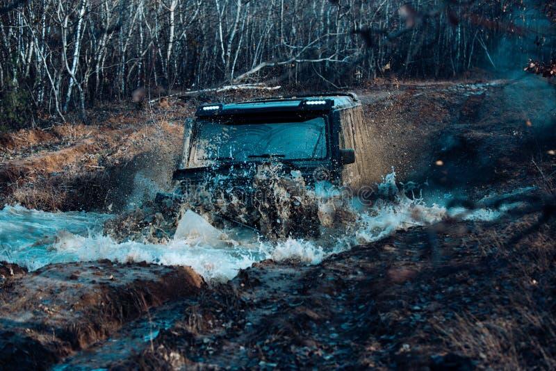 En bil under en tuff av-väg konkurrensdykning i en lerig pöl Extrema helger arkivfoto