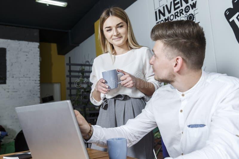 En bild av affärsmannen som sitter på tabellen Han ser handen för bärbar datornad-innehavet nära den Flickan står förutom man och arkivfoton
