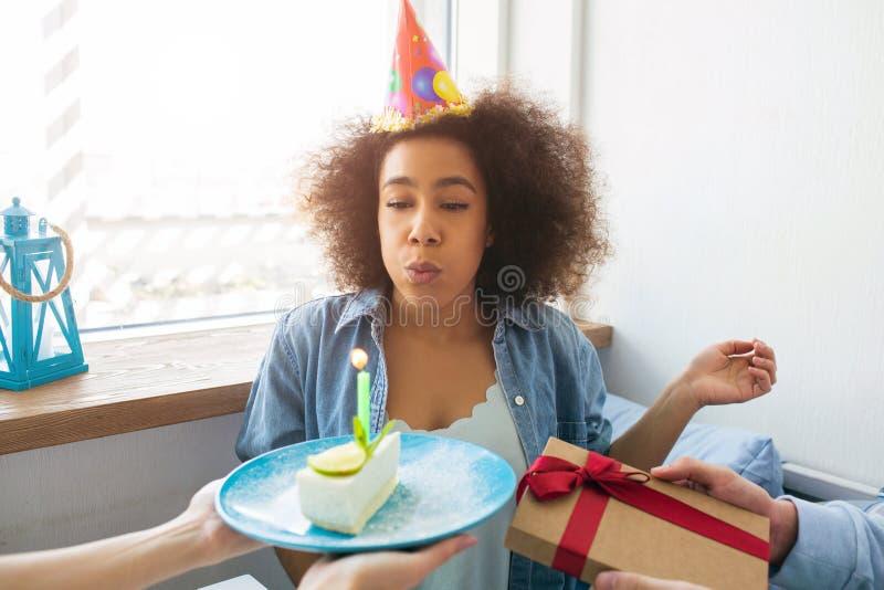 En bild av att blåsa för födelsedagflicka - upp stearinljuset och att få en gåva från hennes vänner arkivbilder