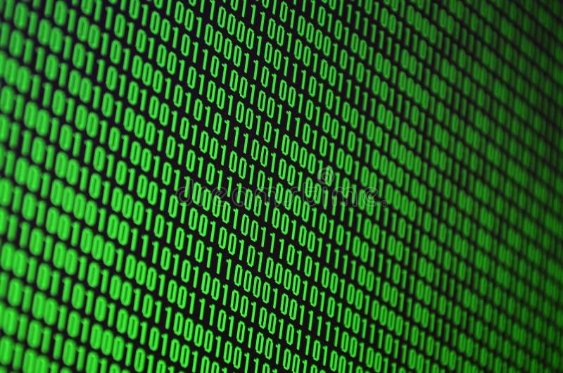En bild av en binär kod utgjorde av en uppsättning av gröna siffror på en svart bakgrund arkivfoto