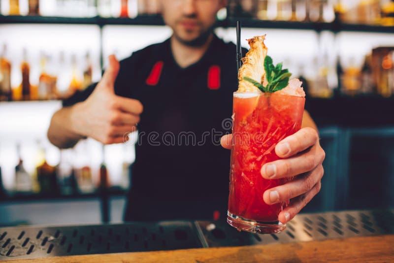 En bild av coctailen som pepareds av bartendern Det har trevlig röd färg Också finns det någon is på överkanten av royaltyfria bilder