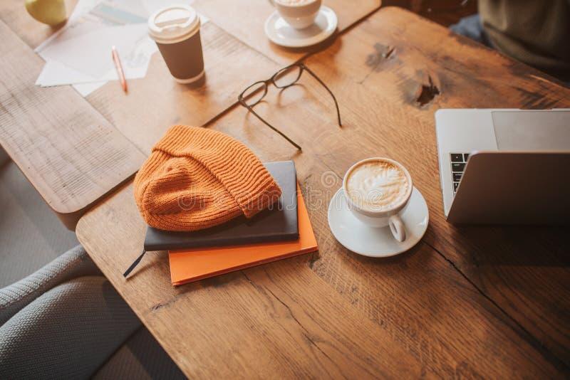 En bild av den moderna minimalistic tabellen med något dricker, kläder och bärbara datorn på den Klipp sikten fotografering för bildbyråer