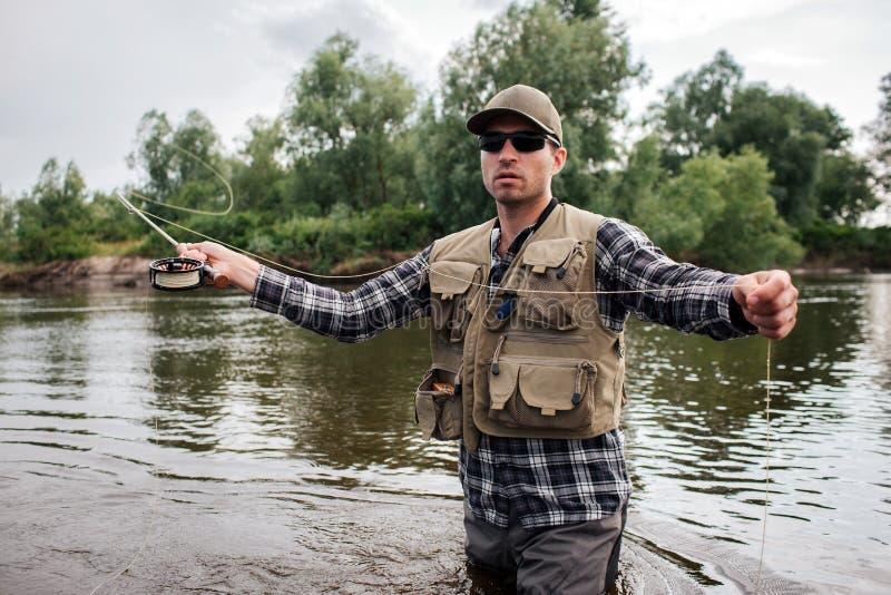 En bild av det brutala och lugna grabbanseendet i vatten och att se framåtriktat Han har den klipska stången i en hand och sked f arkivfoto