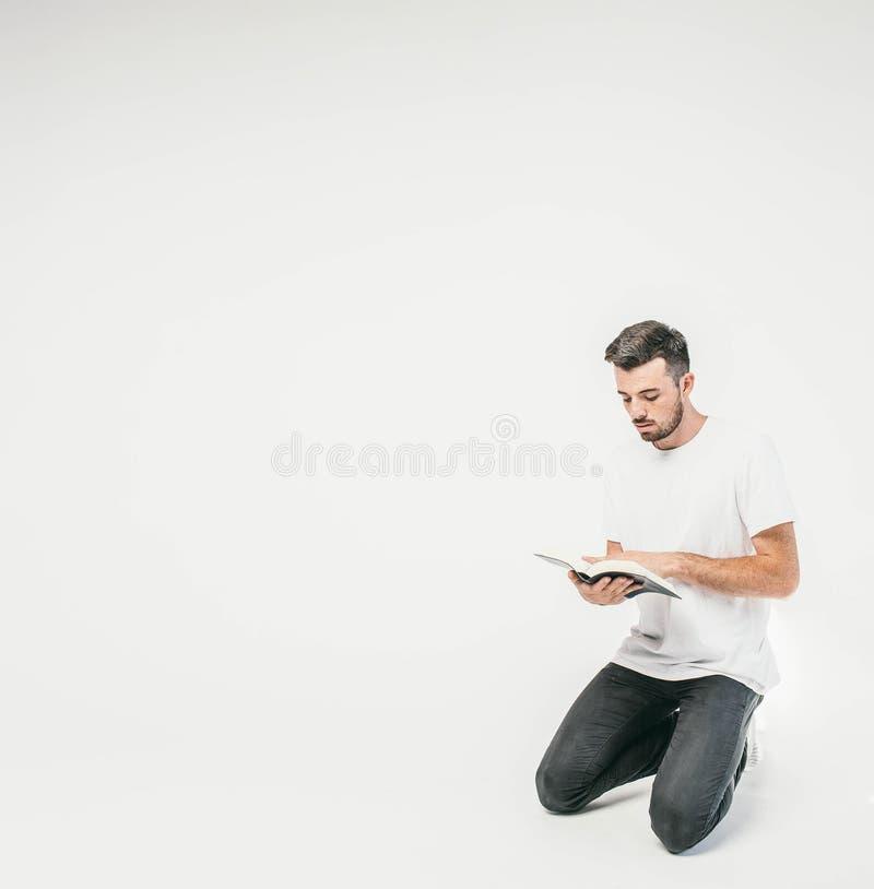 En bild av ett mananseende på hans knä och läsning en bok Boken intreresting mycket, så han kan ` t som koncentreras på arkivfoton