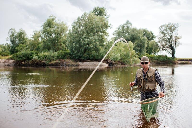 En bild av fiskaren står, i grunt och att se rättfram Han har fluga-fiske i hand En sked visas på royaltyfri foto